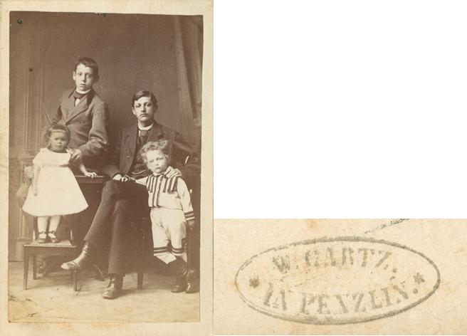 """W. Gartz. Rückseitiger Stempel vergrößert dargestellt, Visitformat. Die Köpfe der beiden kleineren Kinder wurden nachträglich in das Negativ hinein""""gebastelt""""."""