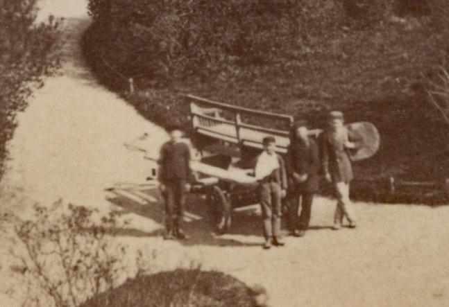 Mitarbeiter der Grünanlagenverwaltung (?) mit einer Parkbank auf dem Wagen